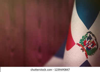 Dominican Republic hanging flag for honour of veterans day or memorial day on pink blurred natural wood wall background. Dominican Republic glory to the heroes of war concept.