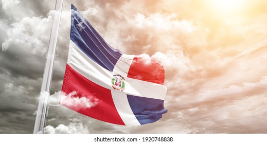 Dominican Republic national flag cloth fabric waving on beautiful grey sky.
