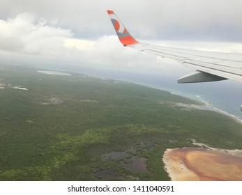Dominican Republic, Punta Cana, June 1, 2019: Aerial view of beautiful landscape with vegetation, caribbean ocean, cloudy sky on horizon, many clouds, wing on left side of GOL airplanes.