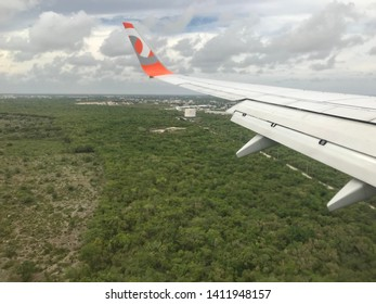 Dominican Republic, Punta Cana, June 1, 2019: Aerial view of the forest in the Caribbean region, landscape with lots of vegetation, cloudy sky on the horizon, wing on the left side of the GOL aircraft