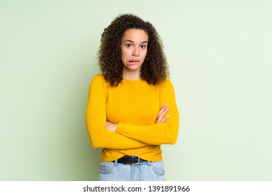 Dominican woman over isolated green background with confuse face expression