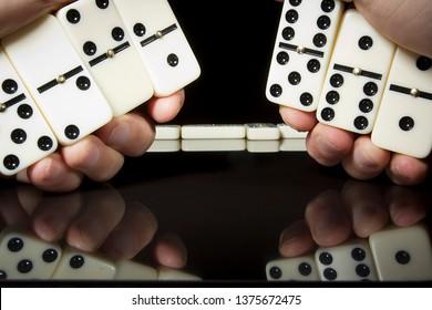 Domino bones in male hands on black reflective background.