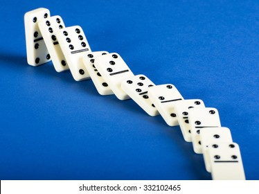 Domino effect with black and white tiles on blue table