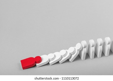 ?oncept of domino effect in business. The fall of the crumbling business starts with one bad employee leader. The domino line of the the man is falling from behind the fall of the red man.