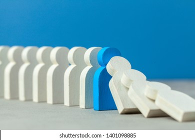 Domino effect in business. One businessman falls and brings down other figures of employees. Prevent the destruction of the system. Crisis manager stops falling dominoes