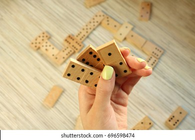 Domino game. Women hand is holding three pieces of domino. Background is full with domino