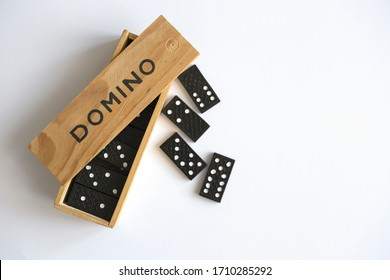Domino game in wooden box on white background, top view. Table game