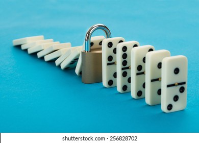 Domino And Lock In A Row Over Blue Background