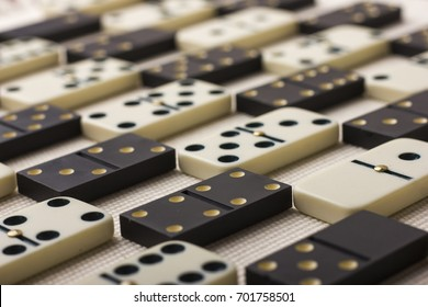 Dominoes are black and white. Light background. The game is tabletop