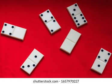 Dominoes Domino bones lie on a red fabric background.