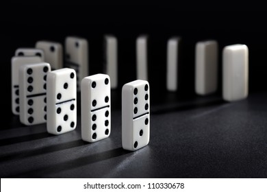 Dominoes lined up ready to fall concept for domino effect, balance and risk