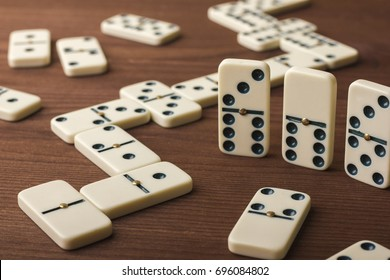 Dominoes on a wooden table. The game is tabletop. Dark background