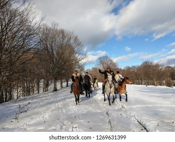 Domnesti, Romania - December 2018: Horsemen wearing traditional Romanian outfit riding their horses on a sunny winter day.