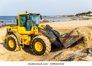 Domsten, Sweden - April 30, 2018: Documentary of everyday life and place. Yellow Volvo wheel loader on the beach moving sand prior to the bathing season.