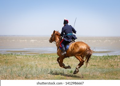 Don Cossack in blue military clothes quickly rides along the coast of the sea with a sabre in his hand