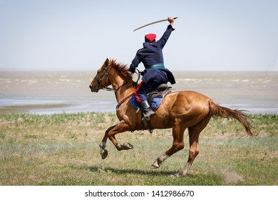 Don Cossack fast rides along the seashore on a horse with a sabre in his hand