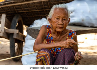 Don Daeng, Laos - April 27, 2018: Senior woman sitting on a dusty path and posing in a remote village of Laos