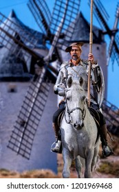 Don Quixote on horseback, with the windmills behind