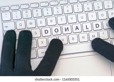 Donald inscription on laptop keyboard. Hacker man using a laptop attacks the web. Cyber Crime Criminal Campaign by Russian Government To Hack Elections In The USA Using Illegal Online Spying.