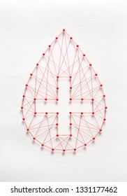 Donate blood concept. Network of pins and threads in the shape of a blood drop symbolising group effort and collaboration for saving lives.