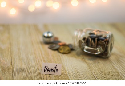 Donate money concept with shiny coins on a glass jar, soft bokeh background on wooden board