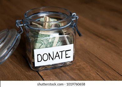 Donate note on money jar / Donation, charity and relief concept