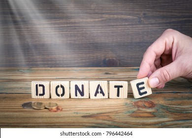 donate. Wooden letters on the office desk, informative and communication background