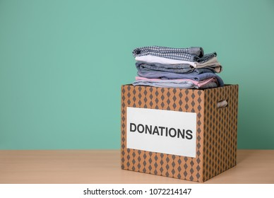 Donation box with clothes on wooden table against color background