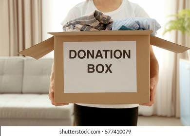 Donation box with clothing in female hands