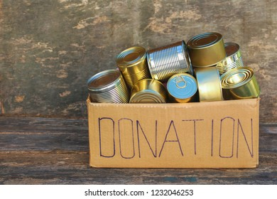 Donation box with different canned food on old wooden background.