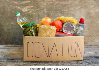 Donation box with food on old wooden background