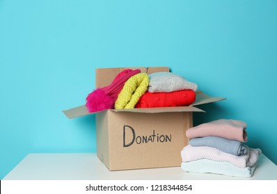 Donation box and knitted clothes on table against color background