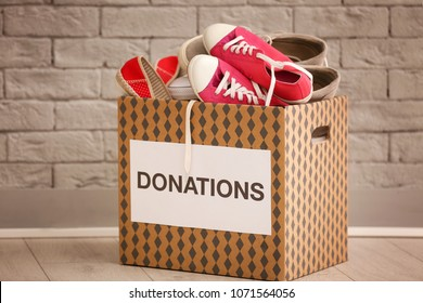 Donation box with shoes on floor against brick wall