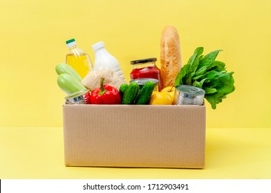Donation Box with Supplies Food for People in Isolation on Yellow Background. Essential Goods: Oil, Canned Food, Cereals, Milk, Vegetables, Fruit