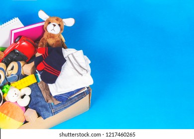 Donation box with toys, books, clothing for charity on blue background