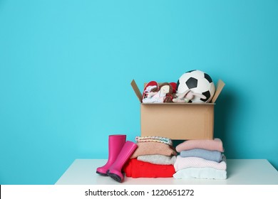 Donation box with toys, knitted clothes and rubber boots on table against color background. Space for text
