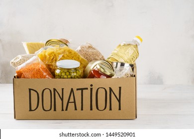 Donation box with various food. Open cardboard box with oil, canned food, cereals and pasta. Copy space.