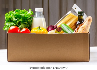 Donation box with various food. Open cardboard box with oil, vegetables, milk, canned food, cereals and pasta. Food delivery concept with space for text.
