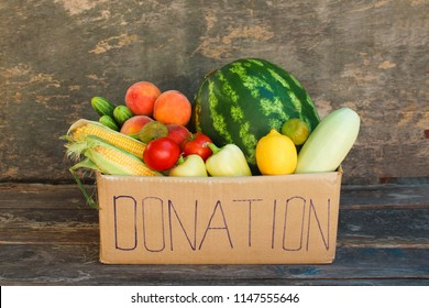 Donation box with vegetables and fruits on the old wooden background.