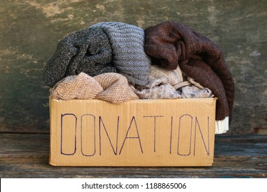 Donation box with warm things on old wooden background.