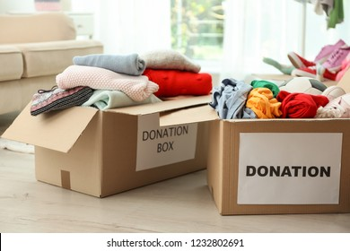 Donation boxes with clothes on floor indoors