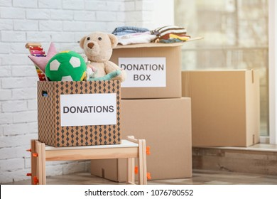 Donation boxes with toys and clothes indoors