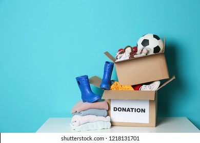Donation boxes with toys, knitted clothes and shoes on table against color background. Space for text