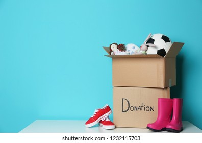 Donation boxes with toys and shoes on table against color background. Space for text