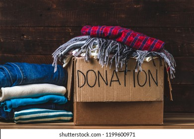 Donation concept. Donation box with donation clothes on a wooden background. Charity. Help for people in need
