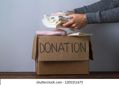 Donation concept. Donation box with donation clothes on a table. Charity. Help for people in need