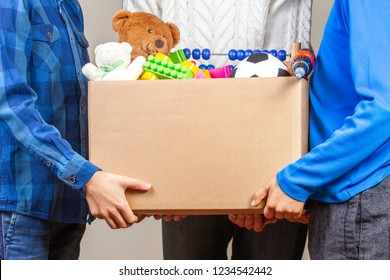 Donation concept. Donate box with clothes, books and toys in family members hand