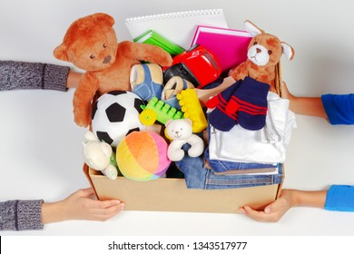Donation concept. Kid hands with donate box with clothes, books, school supplies and toys, white background