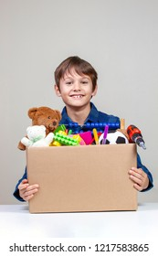 Donation concept. Kid holding donate box with clothes, books and toys