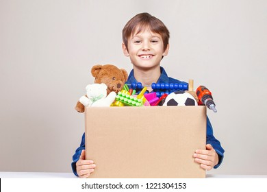 Donation concept. Kid holding donate box with clothes, books, school supplies and toys
